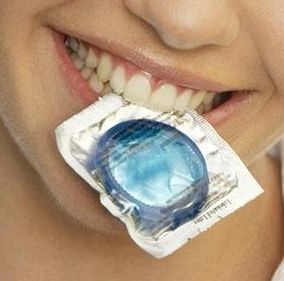 Portrait of a teenage girl holding a condom in her mouth